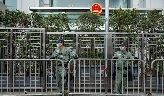 Police officers stand guard at the central government's liaison office in Hong Kong. Photo: Bloomberg