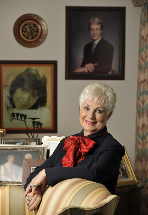 "In this Monday, July 15, 2013 photo, actress Shirley Jones poses for a portrait at her home in Los Angeles. Behind her are portraits of her stepson David Cassidy, left, and son Ryan Cassidy, top. Jones' autobiography, ""Shirley Jones,"" is being released Tuesday, July 23. (Photo by Chris Pizzello/Invision/AP)"