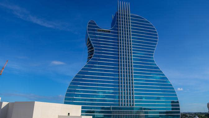 Tampilan bangunan Seminole Hard Rock Hotel & Casino yang menyerupai gitar di Hollywood, Florida, Amerika Serikat, Selasa (22/10/2019). Berbentuk seperti gitar listrik, hotel dengan ketinggian mencapai 20 ribu kaki ini siap menjadi ikon wisata mewah baru. (Zak BENNETT/AFP)