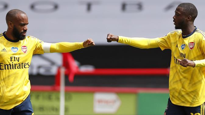 Striker Arsenal Alexandre Lacazette (kiri) merayakan gol Nicolas Pepe ke gawang Sheffield United pada laga Piala FA di Bramall Lane, Minggu (28/6/2020). (AFP/Andrew Boyers)