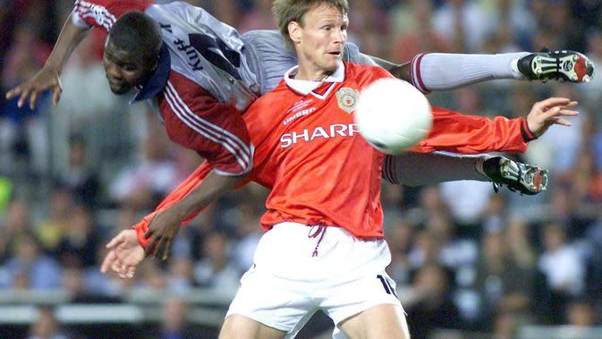 Striker Manchester United, Teddy Sheringham, berebut bola dengan bek Bayern Munchen, Samuel Osei Kuffour, pada laga final Liga Champions di Stadion Camp Nou, Barcelona (26/5/1999). Manchester United menang 2-1 atas Bayern Munchen. (AFP/Eric Cabanis)