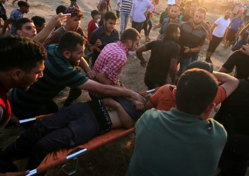 Palestinian paramedics carry an protester injured during a demonstration along the Israeli fence east of Gaza City on September 14, 2018