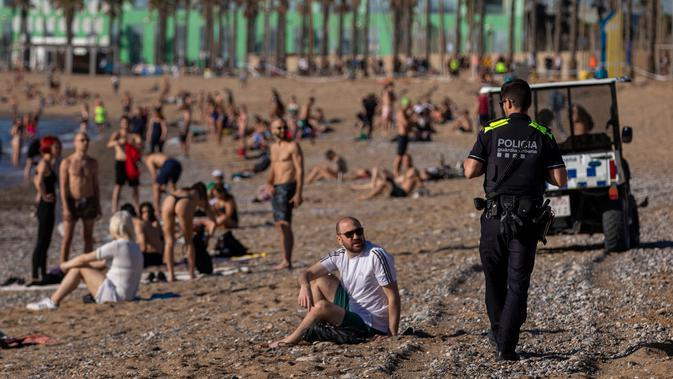 Petugas polisi meminta orang-orang untuk tidak duduk sambil berpatroli di pantai di Barcelona, Spanyol, Rabu, (20/5/2020). Barcelona mengizinkan orang untuk berjalan di pantai untuk pertama kalinya sejak dimulainya penguncian virus coronavirus lebih dari dua bulan lalu. (AP Photo/Emilio Morenatti)