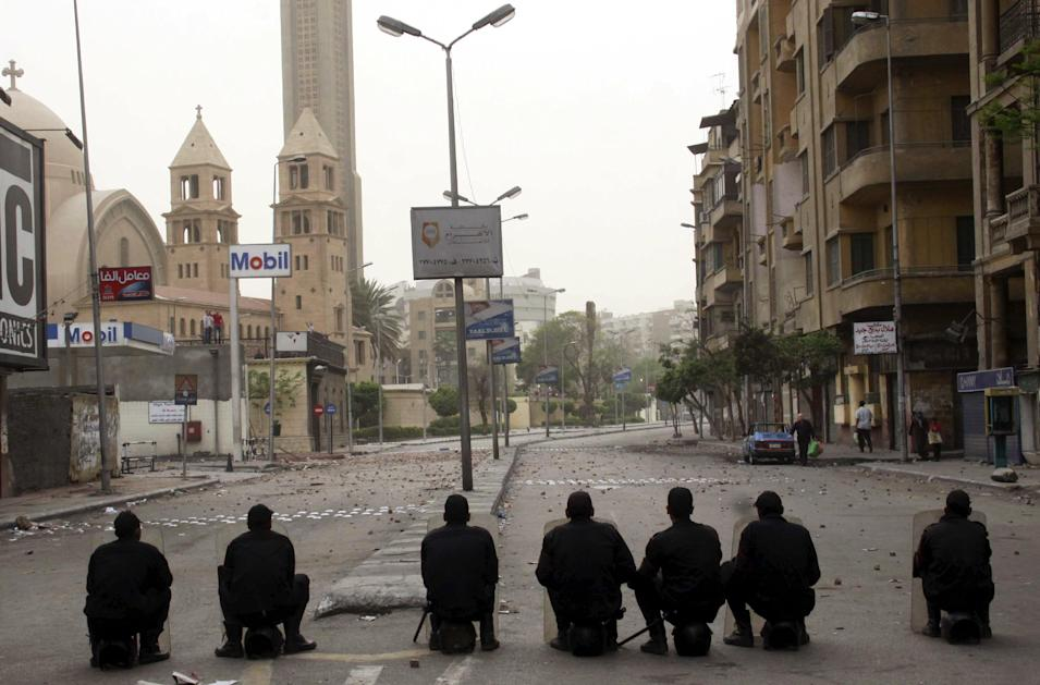 Egyptian riot police watch over the Coptic cathedral in the early hours of Monday, April 8, 2013, in Cairo, Egypt. Christians angered by the killing of four Christians in weekend sectarian violence clashed Sunday and into Monday with a mob throwing rocks and firebombs, killing one and turning Cairo's main Coptic cathedral into a battleground. The clashes raised tempers in an already tense political atmosphere. (AP Photo)