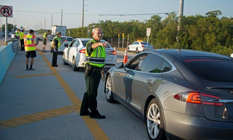 Police man a traffic stop on the route to the Florida Keys, which have been temporarily closed to visitors because of the coronavirus crisis