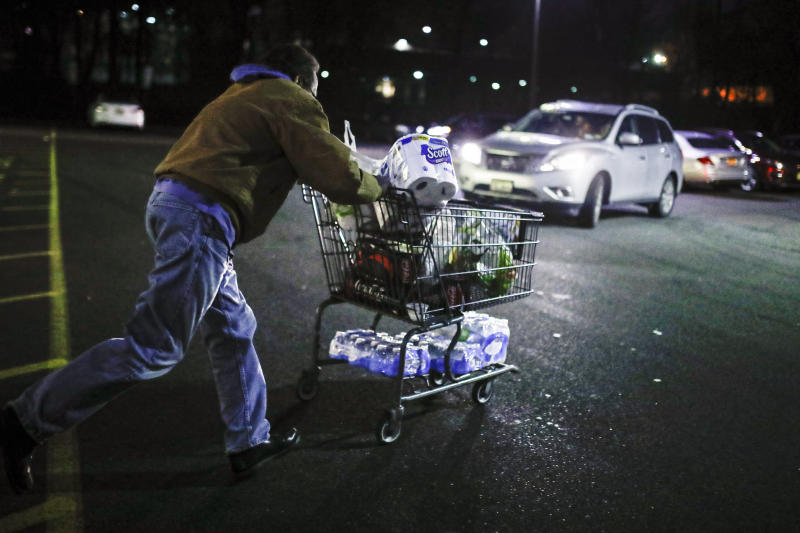 Customer Harry Westhoff, 71, runs his groceries back to his car after shopping at a Stop & Shop supermarket that opened special morning hours to serve people 60-years and older due to coronavirus concerns, Friday, March 20, 2020, in Teaneck, N.J. For most people, COVID-19, the disease caused by the new coronavirus, causes only mild or moderate symptoms, such as fever and cough. For some, especially older adults and people with existing health problems, it can cause more severe illness, including pneumonia. (AP Photo/John Minchillo)