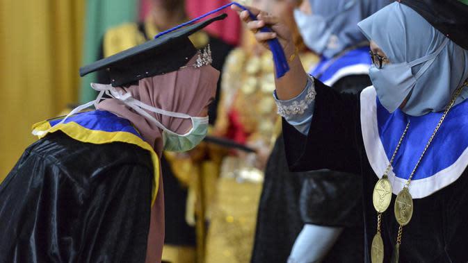 Seorang siswa yang mengenakan masker dan pelindung sebagai tindakan pencegahan terhadap virus Corona COVID-19 mengikuti acara wisuda SMK Farmasi di Banda Aceh (24/9/2020). (AFP/Chaideer Mahyuddin)