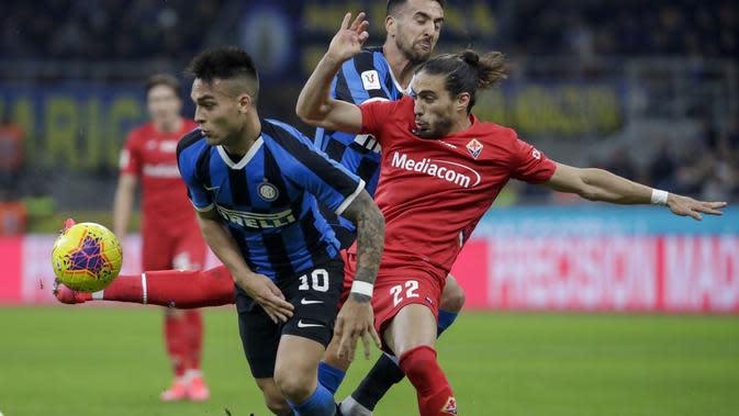Striker Inter Milan, Lautaro Martinez, berebut bola dengan bek Fiorentina, Martin Caceres, pada laga Coppa Italia di Stadion San Siro, Rabu (29/1/2020). Inter Milan menang 2-1 atas Fiorentina. (AP/Luca Bruno)