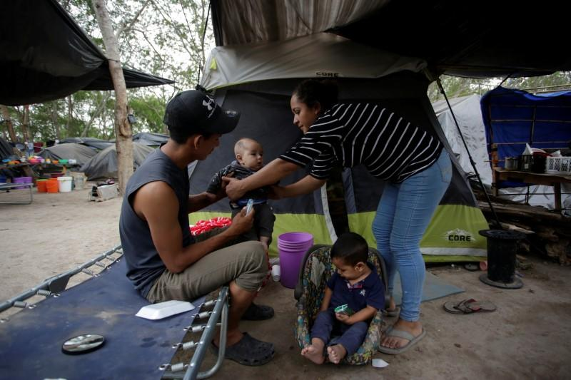 Central American migrants, who are seeking asylum in the U.S., share a moment at an encampment of more than 2,000 migrants, as local authorities prepare to respond to the coronavirus disease (COVID-19) outbreak, in Matamoros