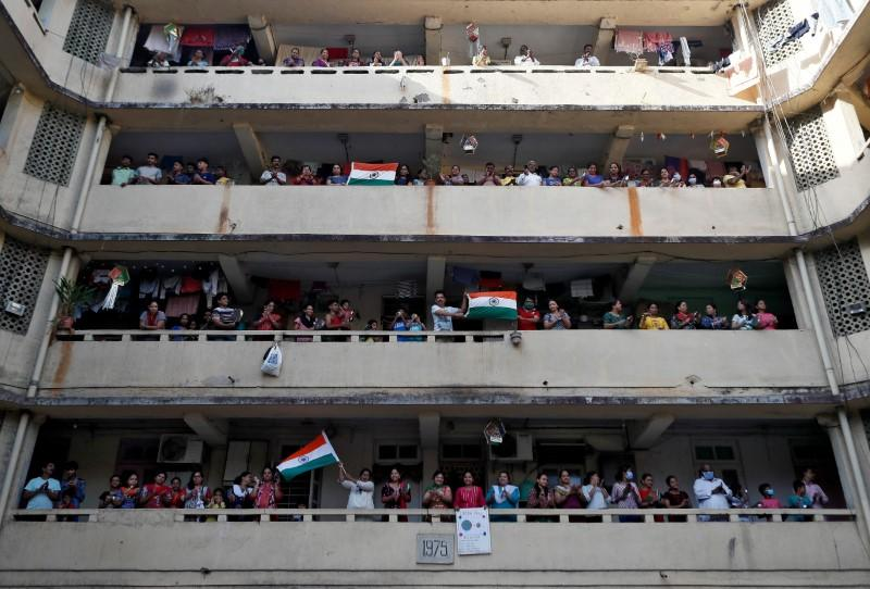 People clap and bang utensils from their balconies to cheer for emergency personnel and sanitation workers who are on the frontlines in the fight against coronavirus, in Mumbai