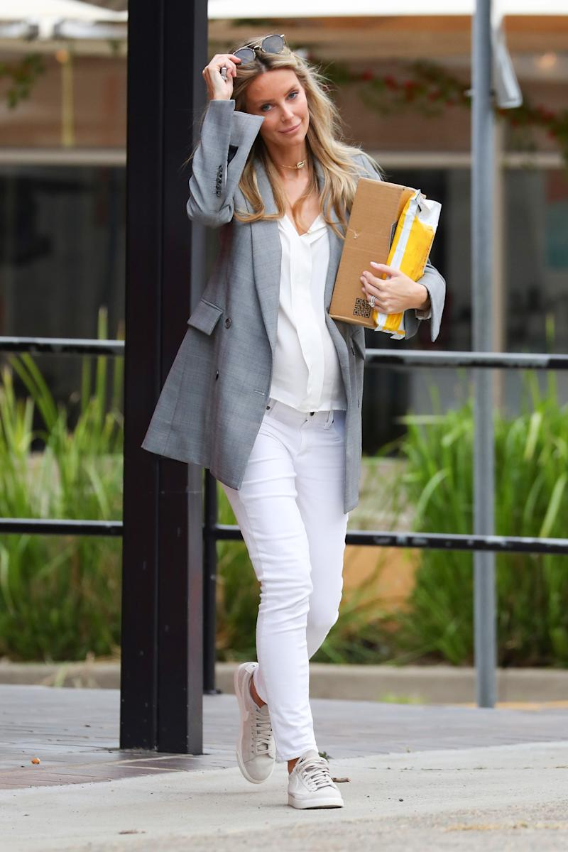 Pregnant Jennifer Hawkins pictured in white jeans and a grey blazer
