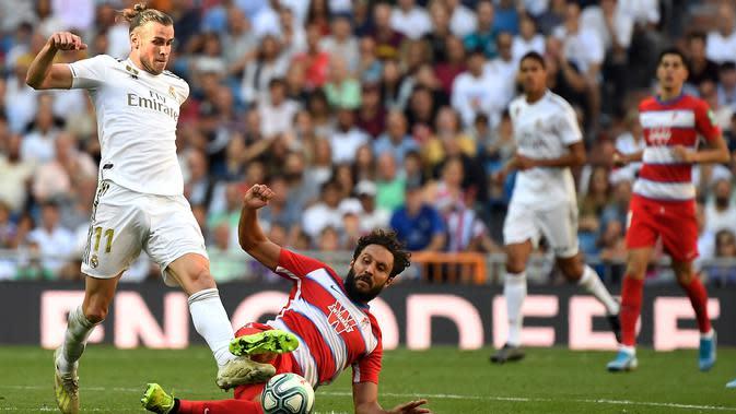 Striker Real Madrid, Gareth Bale, melepas tendangan saat melawan Granada pada laga La Liga Spanyol di Stadion Santiago Bernabeu, Madrid, Sabtu (5/10). Madrid menang 4-2 atas Granada. (AFP/Pierre-Philippe Marcou)