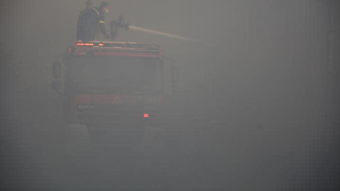 Petugas pemadam kebakaran memadamkan api yang membakar kamp pengungsi Moria di timur laut Pulau Aegean Lesbos, Yunani, Rabu (9/9/2020). Kobaran api juga memusnahkan sebagian besar kamp dan perkebunan zaitun di sekitar bukit. (AP Photo/Panagiotis Balaskas)
