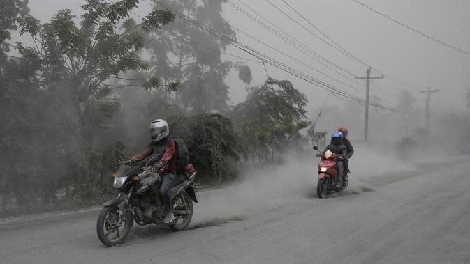 Pengendara motor melintasi jalan yang tertutup abu vulkanik dari gunung Taal untuk mengungsi di Lemery, provinsi Batangas, Filipina, Senin (13/11/2020). Erupsi gunung Taal memaksa puluhan ribu orang mengungsi serta membuat sekolah-sekolah dan toko di Manila tutup. (AP/Aaron Favila)