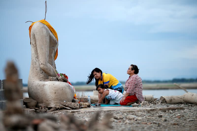 FILE PHOTO: A family prays near the ruins of a headless Buddha statue, which has resurfaced in a dried-up dam due to drought, in Lopburi, Thailand