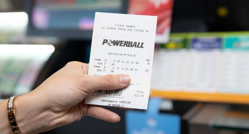 A person holds up a Powerball ticket. The search is on for a second Queensland winner of $50 million.
