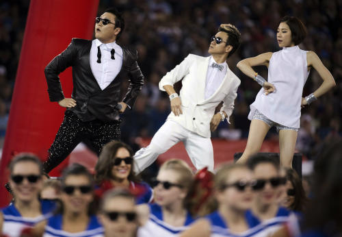"FILE - In this Sunday, Dec. 16, 2012 file photo, South Korean entertainer PSY, left, performs the song ""Gangnam Style"" during halftime of an NFL football game between the Buffalo Bills and Seattle Seahawks, in Toronto. Viral star PSY has reached a new milestone on YouTube. The South Korean rapper's video for ""Gangnam Style"" has reached 1 billion views, the first time any clip has surpassed that mark on the streaming service. PSY passed 1 billion Friday, Dec. 21, 2012, and was already approaching 400,000 more views by mid-morning. (AP Photo/The Canadian Press, Nathan Denette, File)"