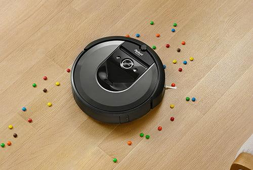 iRobot Roomba i7+ picking up candy on a wood floor