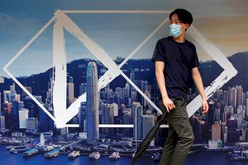 武漢肺炎疫情期間,一名香港民眾走過匯豐銀行廣告。(路透社/達志影像)