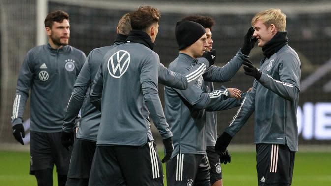 Pemain depan Julian Brandt (kanan) berbincang dengan rekan-rekannya selama sesi latihan tim di Frankfurt am Main, Jerman barat (18/11/2019). Jerman akan bertanding melawan Irlandia Utara pada Grup C Kualifikasi Piala Eropa 2020 di Commerzbank-Arena. (AFP Photo/Daniel Roland)