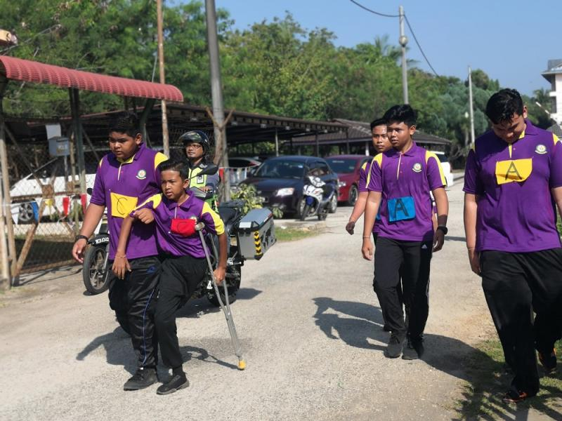 Haikal, aided by his friend, walks along the course during SMK Muadzam Shah's annual school road run.—Picture via Facebook/SMK Muadzam Shah The Official