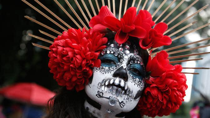 Seorang wanita berdandan ala tengkorak saat mengikuti parade Hari Orang Mati di Mexico City, Meksiko, Sabtu (26/10/2019. Para peserta dalam parade ini mengenakan kostum dan melukis wajah mirip dengan tokoh tengkorak Meksiko yang ikonik, Catrina. (AP Photo/Ginnette Riquelme)