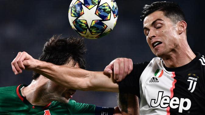 Striker Juventus, Cristiano Ronaldo, duel udara dengan bek Lokomotiv Moscow, Vedran Corluka, pada laga Liga Champions di Stadion Juventus, Turin, Selasa (22/10). Juventus menang 2-1 atas Lokomotiv. (AFP/Marco Bertorello)