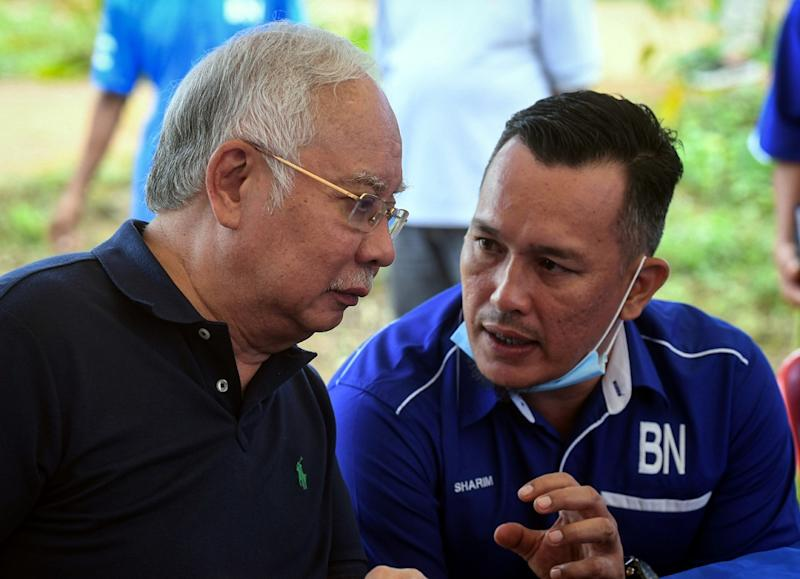 Datuk Seri Najib Razak (left) and Barisan Nasional's candidate for the Chini by-election Mohd Sharim Md Zain are seen chatting during a visit to the Jakun Orang Asli settlement near Pekan June 25, 2020. — Bernama pic