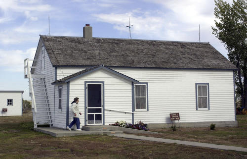 FILE - In this Oct. 10, 2002 file photo Edna Schwab walks toward the front door of the Lawrence Welk farm house in Strasburg, N.D., where Welk taught himself to play accordion. On Friday, Jan. 10, 2014, The state Historical Society is slated to decide whether the state should purchase the bandleader's birthplace. The idea comes two decades after Congress earmarked $500,000 in federal funds to develop a tourist industry in Strasburg. (AP Photo/Will Kincaid, File)