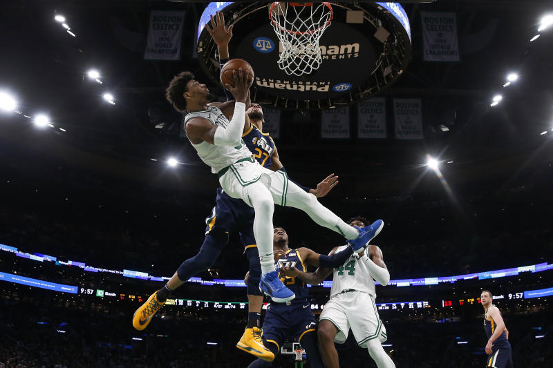 Boston Celtics' Marcus Smart is knocked off balance while going for a shot against Utah Jazz's Rudy Gobert (27) during the fourth quarter of an NBA basketball game Friday, March 6, 2020, in Boston. (AP Photo/Winslow Townson)