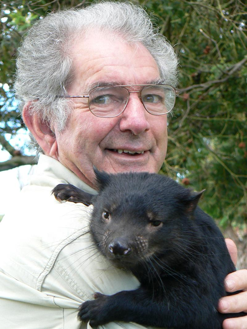 Bruce Englefield with grey hair and glasses poses with a Tasmanian devil in his arms. He developed the app to reduce roadkill.