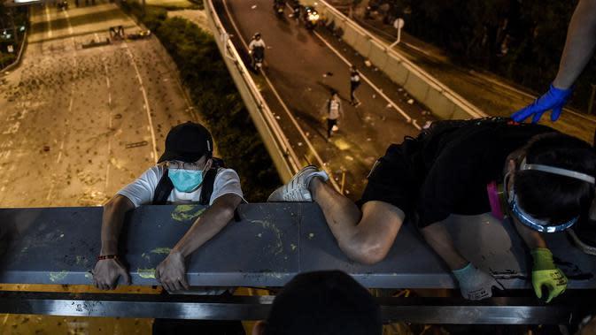 Demonstran menuruni jembatan menggunakan tali untuk melarikan diri dari Universitas Politeknik Hong Kong di Distrik Hung Hom, Hong Kong, Senin (18/11/2019). Lusinan demonstran melarikan diri dari Universitas Politeknik Hong Kong yang dikepung polisi selama berhari-hari. (Ye Aung Thu/AFP)
