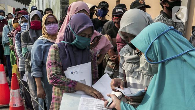 Warga antre untuk menerima Bantuan Sosial Tunai (BST) di Desa Cikande, Kecamatan Jayanti, Kabupaten Tangerang, Banten, Selasa (23/6/2020). Bantuan sebesar Rp 600 ribu per keluarga tersebut diharapkan bisa dimanfaatkan untuk membeli kebutuhan mendesak. (Liputan6.com/Johan Tallo)