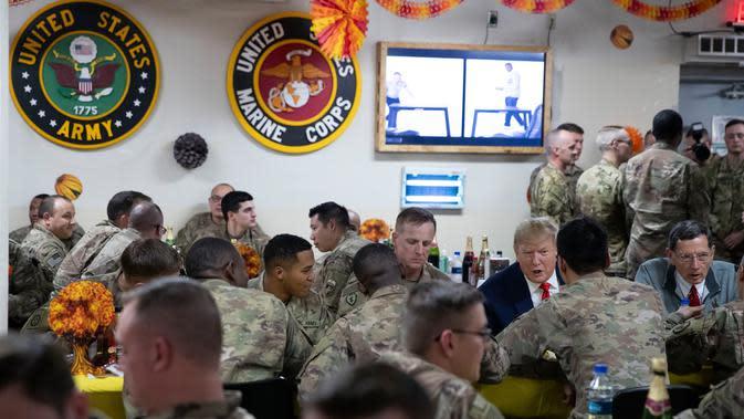 Presiden Amerika Serikat Donald Trump makan malam bersama para tentara saat mengunjungi Pangkalan Udara Bagram, Afghanistan, Kamis (28/11/2019). Kunjungan dadakan Trump pada hari Thanksgiving tersebut mengejutkan pasukan AS yang bertugas di Afghanistan. (AP Photo/Alex Brandon)