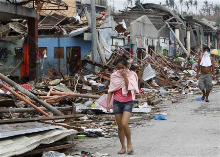 Residents cover their noses as they walk past devastated houses after super typhoon Haiyan hit Tacloban