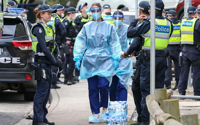 Medical staff wearing PPE enter the Flemington Public housing flats in Melbourne -  Asanka Ratnayake/Getty Images AsiaPac