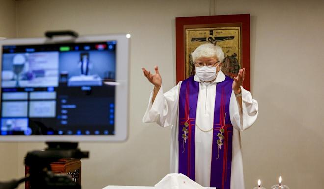 A priest conducts a service streamed online for church-goers, after the Roman Catholic Diocese of Hong Kong temporarily suspended public masses at churches in March. Photo: Reuters