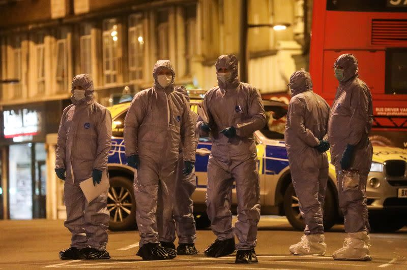 Police forensics officers are seen near a site where a man was shot by armed officers in Streatham, south London