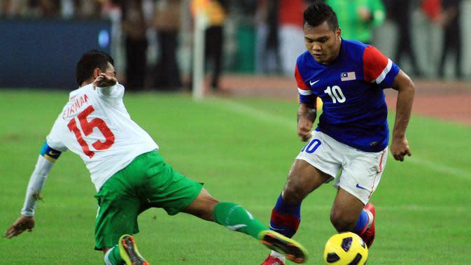 Penyerang Malaysia, Safee Sali, berusaha melewati kapten Timnas Indonesia, Firman Utina, pada final leg pertama Piala AFF 2010. (AFP/Kamarul Akhir)