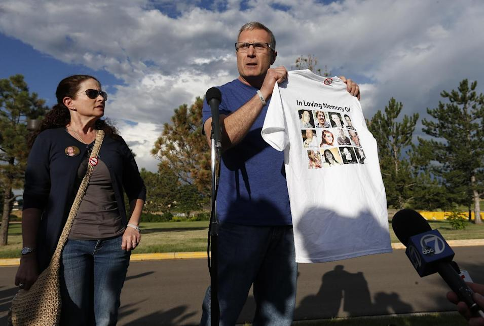 Tom Teves and his wife Caren, who lost their son Alex in the 2012 Aurora movie theatre massacre, speak to members of the media while holding a t-shirt bearing the images of the twelve who were killed in the shooting, after the two attended the reading of the verdicts in the trial of  theater shooter James Holmes, at the Arapahoe County District Court, in Centennial, Colo., Thursday, July 16, 2015. A Colorado jury on Thursday convicted Holmes of killing 12 moviegoers and wounding dozens of others in a suburban Denver movie theater in 2012. (AP Photo/Brennan Linsley)