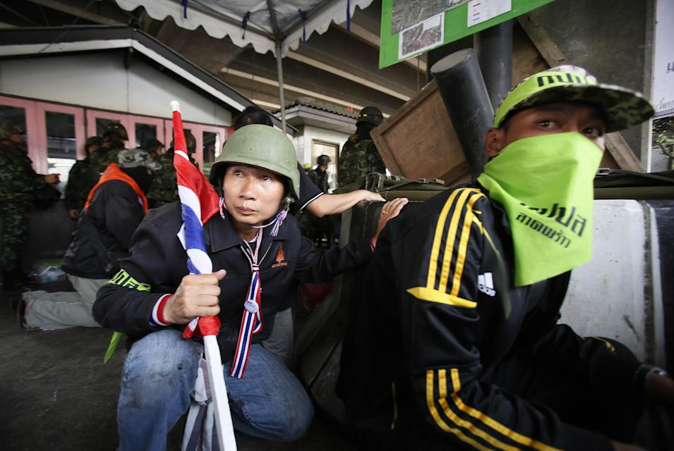 Anti-government protesters duck for cover during a gun fight with pro-election supporters in Bangkok, Thailand, Saturday, Feb. 1, 2014. Gunfire rang out at a major intersection in Thailand's capital on Saturday as clashes between protesters and government supporters erupted on the eve of tense nationwide elections. At least seven people are reported wounded, including an American photojournalist. (AP Photo/Wally Santana)