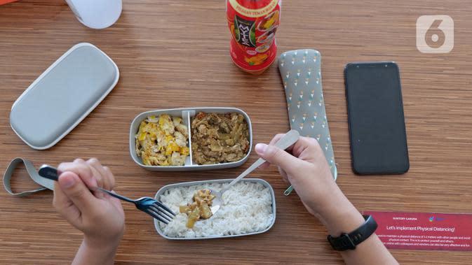 Karyawan menggunakan alat makan pribadi saat menikmati makan siang di ruang istirahat kantor Suntory Garuda, Jakarta, Senin (8/8/2020). Suntory Garuda menerapkan protokol Kesehatan, salah satunya kapasitas karyawan hanya dibolehkan sebanyak 50 persen. (Liputan6.com/Herman Zakharia)