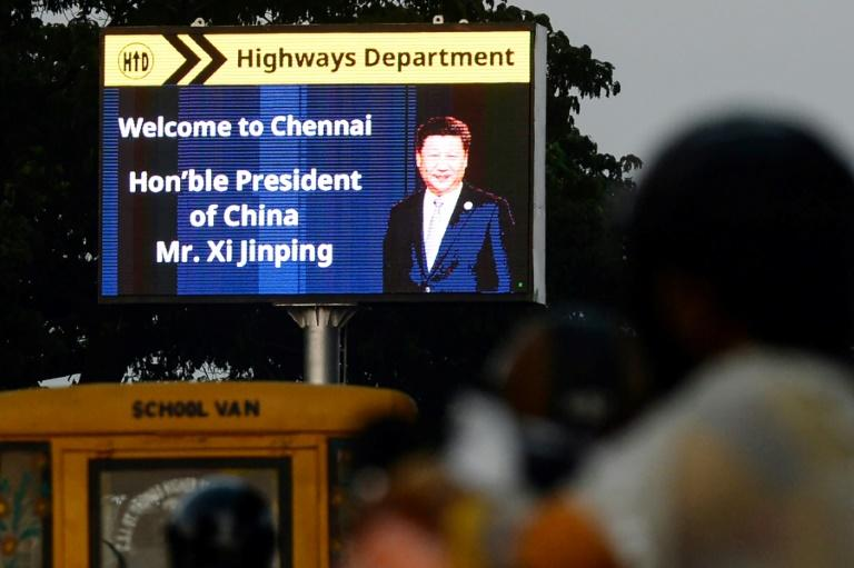 Commuters drive past a sign welcoming China's President Xi Jinping in Chennai, India, ahead of a summit with his Indian counterpart Narendra Modi while the Kashmir issue places the two countries' ties under increased strain