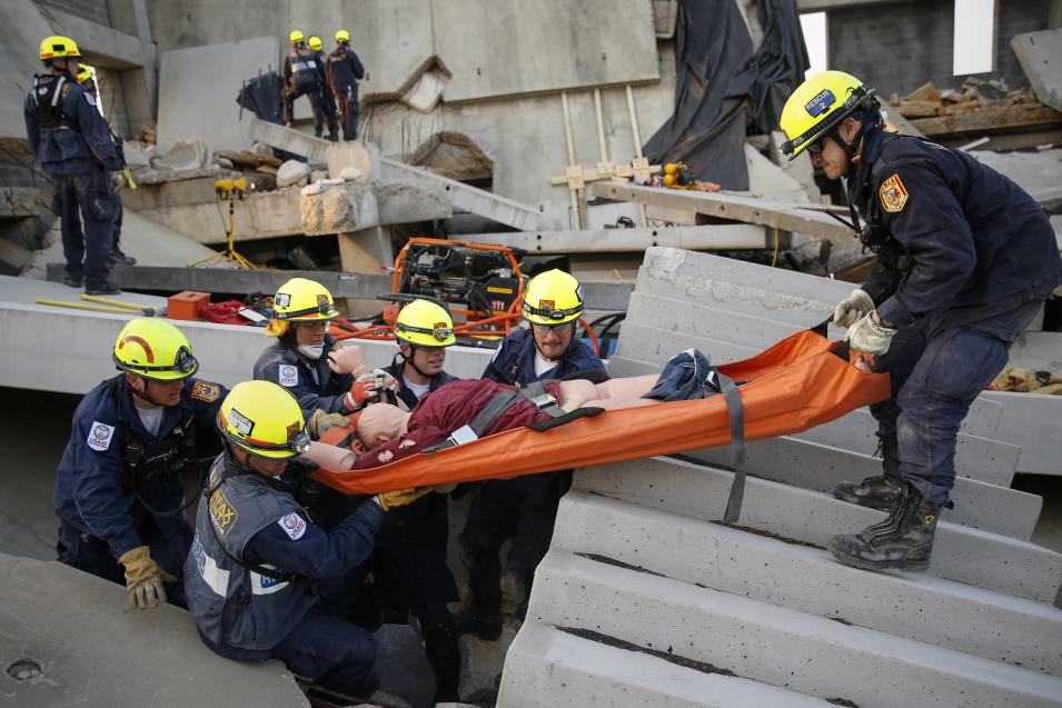 Rescue specialists for USA-1 carry a victim rescued from the scene of a mock disaster area during a training exercise at the Guardian Center in Perry, Georgia