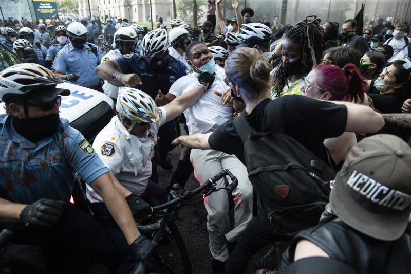 Police and protesters clash Saturday, May 30, 2020, in Philadelphia, during a demonstration over the death of George Floyd. Protests were held throughout the country over the death of Floyd, a black man who died after being restrained by Minneapolis police officers on May 25.. (AP Photo/Matt Rourke)