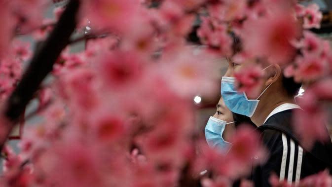 Orang-orang yang mengenakan masker berjalan melewati dekorasi perayaan Imlek Tahun Tikus Logam di Hong Kong, 24 Januari 2020. Pemerintah China memutuskan menutup seluruh akses masuk dan keluar Kota Wuhan untuk mencegah penyebaran wabah virus corona. (AP/Kin Cheung)