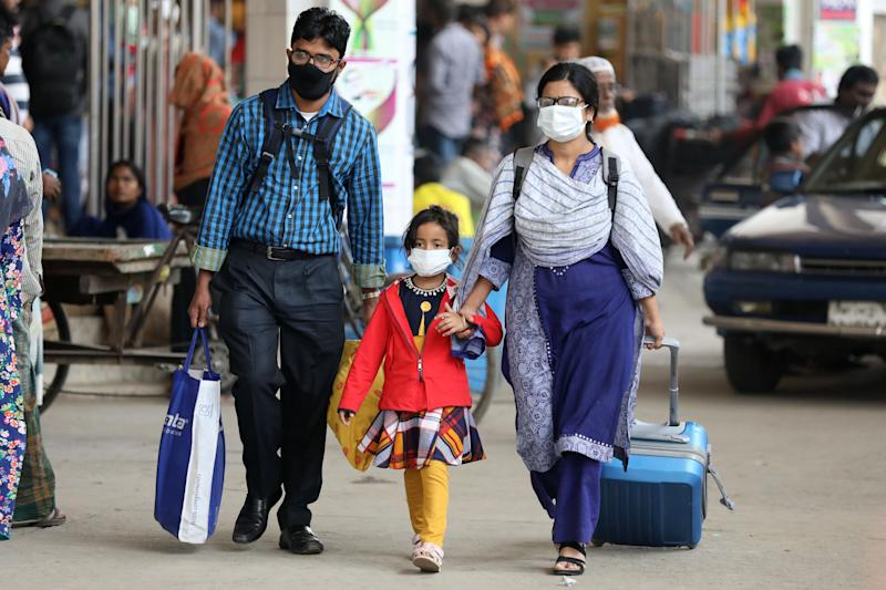 A Bangladeshi family wearing facemasks amid fears of the spread of COVID-19 novel coronavirus, walk through a street, in Dhaka on March 9, 2020. (Photo by Mehedi Hasan/NurPhoto via Getty Images)