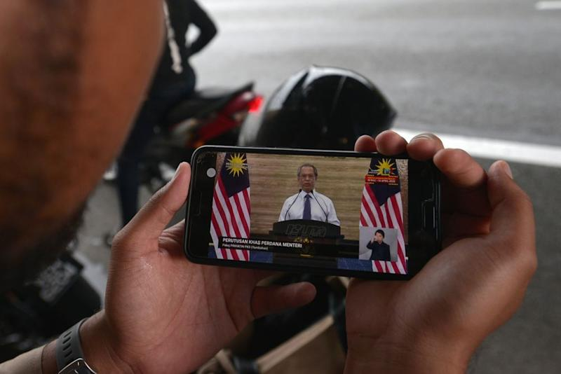 People watching and listening to the prime minister's live telecast in Kuala Lumpur on April 06, 2020. — Picture by Miera Zulyana