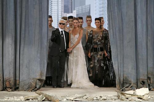 German fashion designer Karl Lagerfeld, left, surrounded by models, acknowledges applause following the presentation of the Haute Couture Fall-Winter 2013-2014 collection he designed for Chanel, Tuesday, July 2, 2013 in Paris. (AP Photo/Francois Mori)