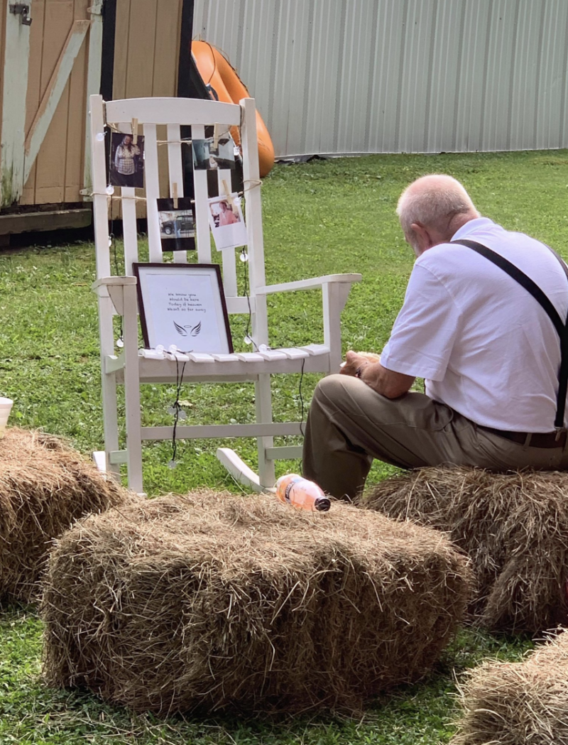 The grandfather sits alone on a hay bail in front of a rocking chair serving as a memorial for his late wife.
